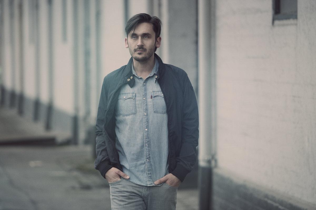 Jesper Colfach er sanger og sangskriver i bandet Colfach, og optræder denne aften i en ren akutisk singer-songwriter form med guitar og ukulele